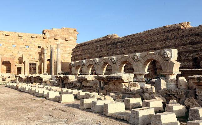 Libya'daki erkekler, 18 Aralık 2016'da Libya'nın başkenti Trablus'un 130 km doğusundaki Al Khums'taki antik Roma kenti olan Leptis Magna'daki amfitiyatroyu gözetirken.