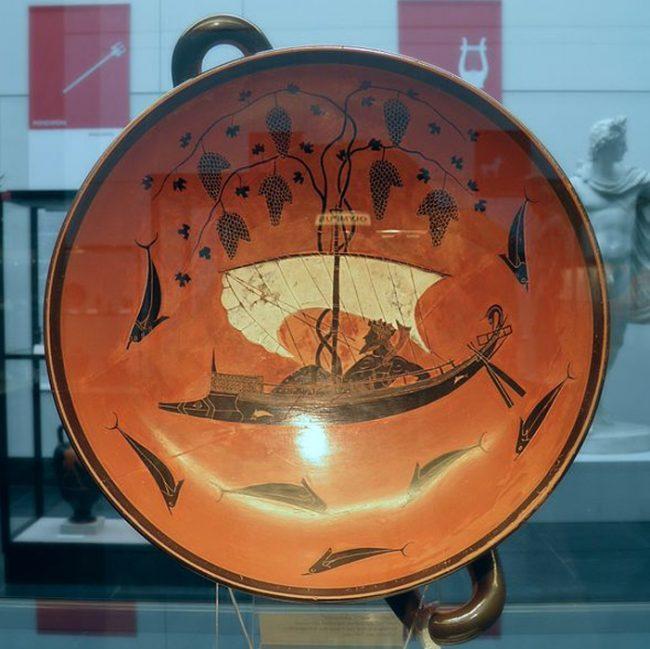 Exekias[4] tarafından boyanan siyah figürlü ünlü bir kylix[5]. Şarap tanrısı Dionysos bir gemide tasvir ediyor. Bir efsanede korsanların onu kaçırmak istediği ancak Dionysos'un hepsini yunuslara çevirdiği ve gemi direğinden çıkan asma yapraklarının yelken vazifesi gördüğü anlatılır.(Carole Raddato/CC BY SA 2.0)